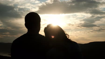Silhouettes of a young couple at sunset. A woman puts her head on her boyfriends shoulder.