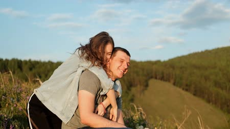 romantik : A young woman hugs her boyfriend and laughs. Happy couple in the Park. Stok Video