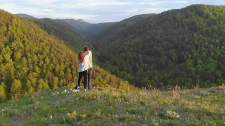 Сибирь : Aerial shot of a young couple standing on top of a mountain on enjoy a beautiful view of the valley. A woman hugs her boyfriends shoulders.
