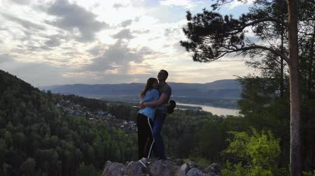 A young couple stand on the edge of a cliff and kiss.