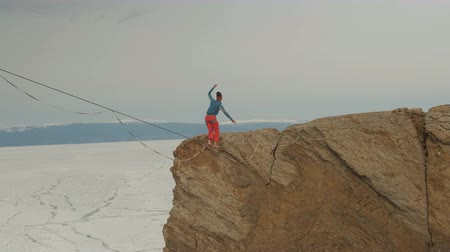 tightrope : A young woman is on the slackline at high altitude.