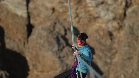 The woman climber is sent up the rope across the chasm.