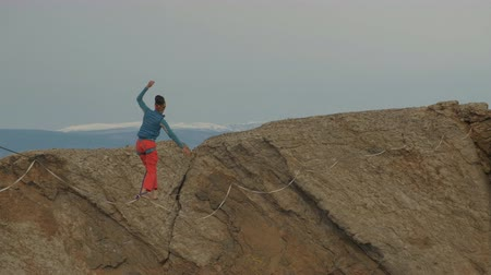 equilibrium : A young woman is on the slackline at high altitude.