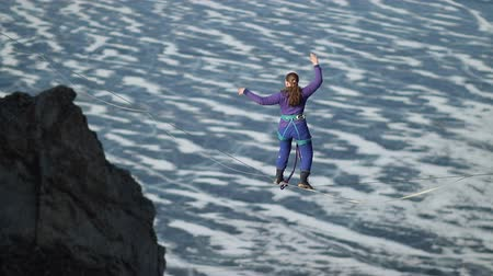 Una giovane donna è in slackline in alta quota. Filmati Stock