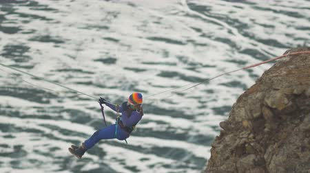 dangle : Climber crossing the gorge on a rope. Stock Footage