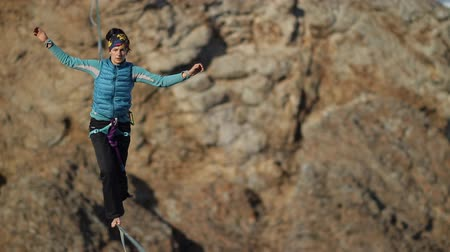 fearless : A young woman is on the slackline at high altitude.