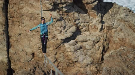 overcome : A young woman is on the slackline at high altitude.