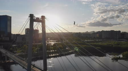 equilibrium : A man walks on a rope stretched between the supports of the bridge at high altitude.