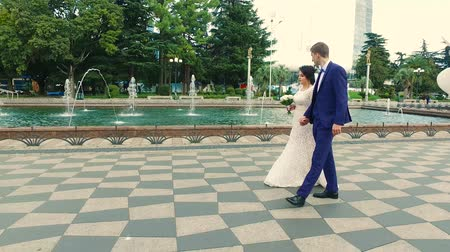 Bride and groom walk along the promenade along the fountains in Batumi Dostupné videozáznamy