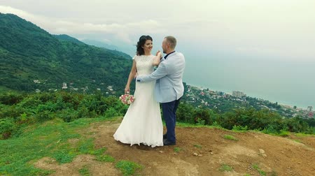 Bride and groom stand on cliff against mountains Dostupné videozáznamy