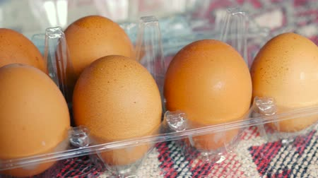Brown eggs lie in a row in a package, dark eggs.