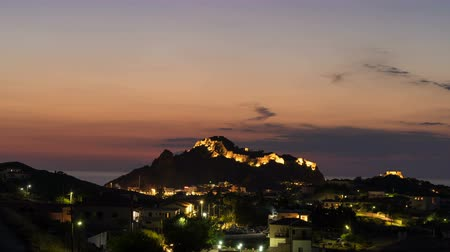 deep seaport : Time lapse of nightfall in Myrina, Greece with scenic lights at Byzantine Castle in Lemnos