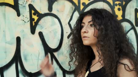 hanedan arması : Female model with curly dark hair posing against graffiti wall outdoors Stok Video
