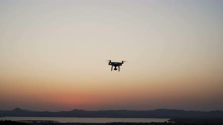 spying : Drone quadcopter hover above sea coast and filming