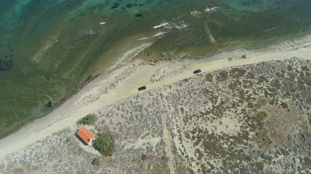 ahead : Drone following cars driving slow at rocky beach coastal road in Lemnos,Greece