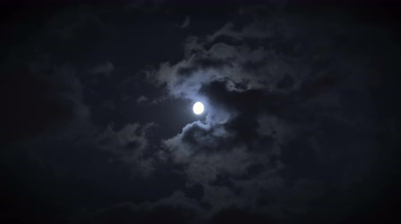 fáze : Night sky with clouds glowing from full moon and partly covering it