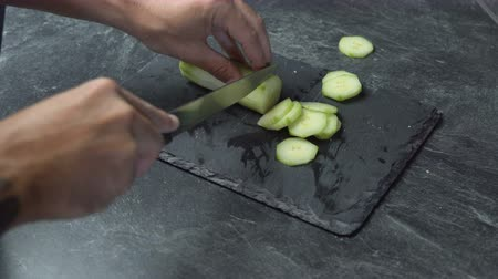 gıda maddesi : Close up on male hands cutting cucumber, making salad. Chef cutting vegetables. Stok Video