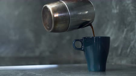 pitcher : Close shot of hand pouring black coffee in big cup early in the morning