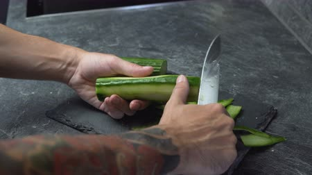 soyulması : Close shot of male hands with tattoos peeling fresh cucumber with long knife Stok Video