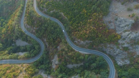 koşullar : Top view from drone following white truck and car driving along mountain winding road in sunny summer day
