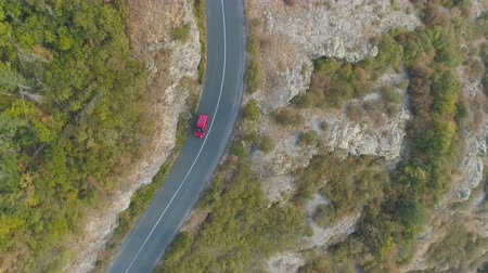 pista de corrida : Drone follow red car driving alone rocky mountain road in autumn day Vídeos