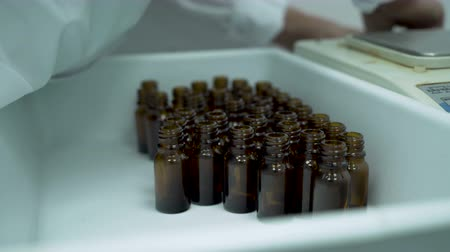 Scientist arranging small bottles in container at Hemp CBD laboratory