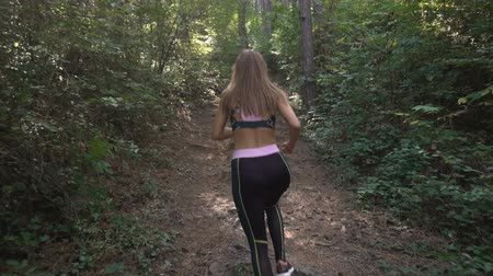 Slow motion video of fit woman trail running in the forest on hard terrain