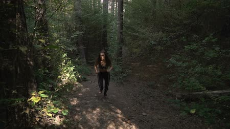Front view, slow motion footage of fit, young woman with brown long hair trail running in forest in the morning