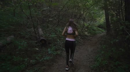 Sports brunette girl trail running in the woods, slow motion footage