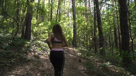 Fitness sport girl in sportswear running in forest, outdoor sport. Slow motion footage