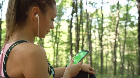 Beautiful girl in sportswear sitting on a bench in the forest, relaxing and listening music from phone Dostupné videozáznamy