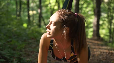 apertado : Attractive girl listening music on earphones while working out early in the morning in the park