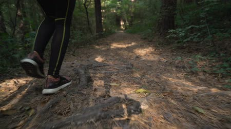 apertado : Close view of woman feet running in the forest on hard terrain, wearing sport shoes
