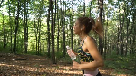 apertado : Athletic girl running in the forest and holding water bottle and listening music
