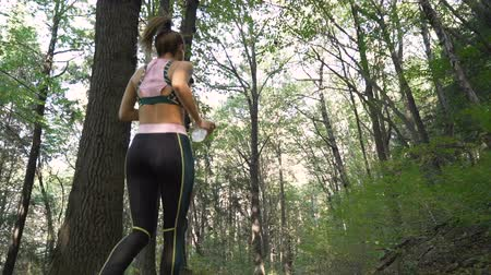 apertado : Tracking camera of girl running in the forest, jumping off tree trunks on hard terrain