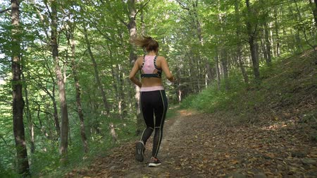 apertado : Slow motion tracking camera of fitness girl running on forest path in the autumn
