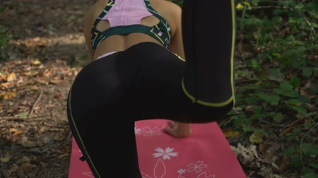 apertado : Back view of fit, attractive woman doing hip exercise with legs on yoga mat outdoors
