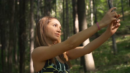 Gorgeous fitness girl taking selfie with smartphone in the forest