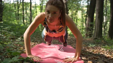 apertado : Active girl, concentrated in workout doing push ups on pink Pilates mat in the forest