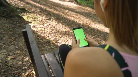 Back view of Beautiful girl with earphones using smartphone with green screen, outdoors in the park