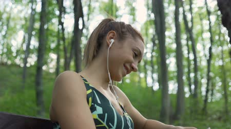 Joyful girl with ponytail, listening music with earphones and laughing. Jogger resting on a bench in the park