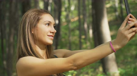 Close view of smiling brunette girl taking selfie picture with phone in the park Dostupné videozáznamy