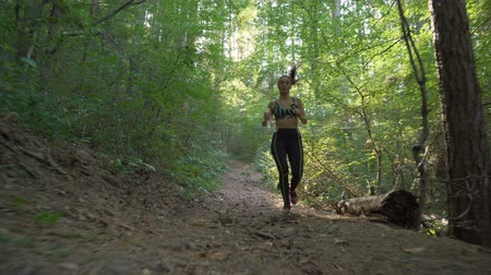 pilates : Female jogger with earphones holding water bottle and running cross in the forest