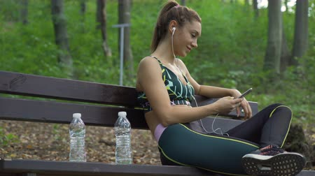 Female jogger with trail running shoes and sportswear relaxing on a bench, listening music. Water bottles next to a fitness girl Dostupné videozáznamy