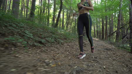 apertado : Attractive girl trail running on hard forest terrain, holding bottle with water