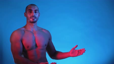 břišní : Fitness model showing his body, isolated on blue background