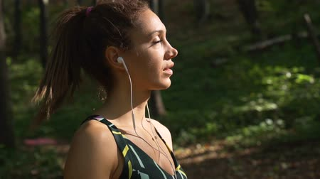 soñar despierto : Close view of fitness girl with white earphones thinking and staring at the sun Archivo de Video