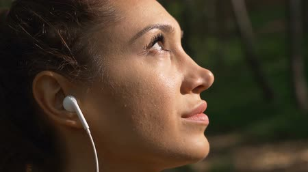 sonhar acordado : Active girl with white earphones daydreaming staring at the sun