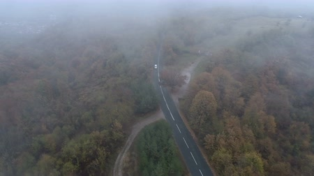 маркировка : Drone follows white car driving on foggy mountain road in the autumn Стоковые видеозаписи