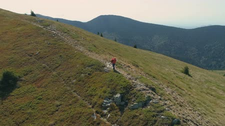 suceder : Aerial view of hiker in red jacket picking up his bag and continuing his adventure